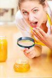 Femme inspectant le miel avec la loupe Photos libres de droits