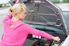 Femme inspectant le moteur de voiture cassé Photo stock