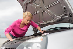 Femme inspectant le moteur de voiture cassé Photographie stock