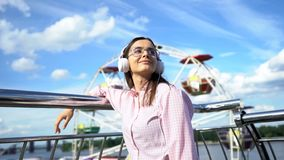 Femme inspirée écoutant la musique dans des écouteurs, observant avec confiance à l'avenir image libre de droits