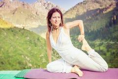 Femme inspirée faisant l'exercice du yoga à la gamme de montagne Photographie stock