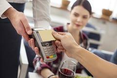Femme inspirée observant son ami payer par la carte de crédit Image libre de droits