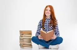 Femme inspirée s'asseyant près de la pile des livres et de la lecture Image libre de droits