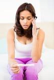 Femme intéressée regardant son essai de grossesse photo libre de droits