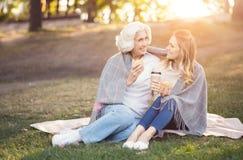 Femme intelligente appréciant la conversation avec la vieille mère en parc Photos libres de droits