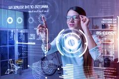 Femme intelligente souriant et touchant ses verres tout en regardant l'écran images libres de droits