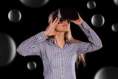Femme intriguée dans le casque de port de la réalité virtuelle 3D de chemise grise Photo libre de droits