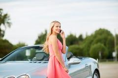 Femme invitant le smartphone à la voiture convertible photographie stock libre de droits