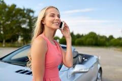 Femme invitant le smartphone à la voiture convertible photos stock