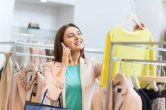 Femme invitant le smartphone au magasin d'habillement Images libres de droits