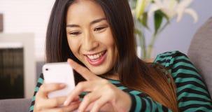 Femme japonaise à l'aide du smartphone sur le divan photo libre de droits