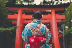 Femme japonaise dans le kimono devant un tunnel de Torii image libre de droits