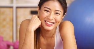Femme japonaise de sourire se reposant sur la boule de séance d'entraînement image libre de droits