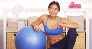 Femme japonaise de sourire se reposant sur la boule de séance d'entraînement photos libres de droits