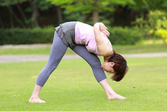 Femme japonaise faisant la pose latérale intense de bout droit de YOGA photos stock
