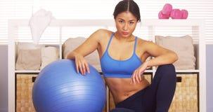 Femme japonaise forte se reposant sur la boule d'exercice photos stock