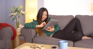 Femme japonaise mignonne à l'aide du comprimé sur le divan photo stock
