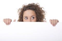 Femme jetant un coup d'oeil derrière le panneau-réclame emtpy Photo stock