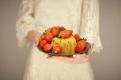 Femme, jeune mariée de boho tenant peu de gâteau d'un plat avec des fraises Photo stock
