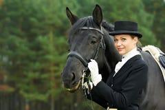 Femme jockey d'amazone dans l'uniforme avec le cheval Photographie stock libre de droits