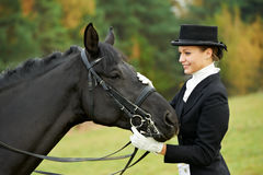 Femme jockey d'amazone dans l'uniforme avec le cheval Images stock