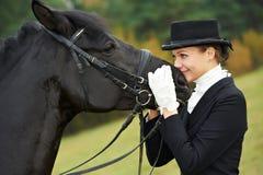 Femme jockey d'amazone dans l'uniforme avec le cheval Photographie stock