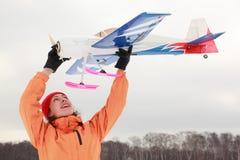 Femme joué avec l'avion à l'hiver Photographie stock libre de droits