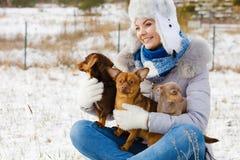 Femme jouant avec des chiens pendant l'hiver images stock
