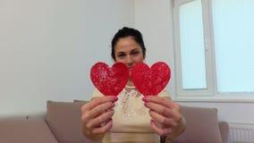 Femme jouant avec deux coeurs de papier rouges banque de vidéos