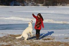 Femme jouant avec le chien blanc en hiver photo stock