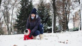 Femme jouant avec le chien de roquet d'amusement en parc neigeux Chien habillé comme Santa Claus dans un costume rouge avec un ca banque de vidéos