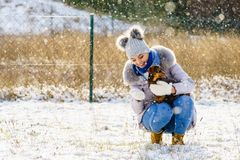 Femme jouant avec le chien pendant l'hiver photo stock