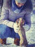 Femme jouant avec le chien pendant l'hiver photographie stock