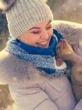 Femme jouant avec le chien pendant l'hiver images stock