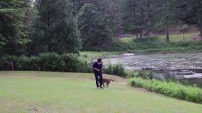 Femme jouant avec le chien sur le lac banque de vidéos
