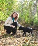 Femme jouant avec le chiot noir de chien d'arrêt de Labrador Image libre de droits