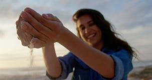 Femme jouant avec le sable sur la plage 4k clips vidéos