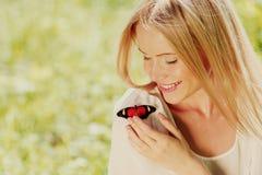 Femme jouant avec un papillon Image stock