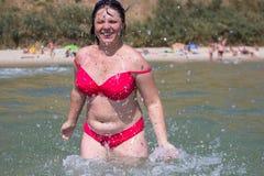Femme jouant dans l'eau de mer Photo stock