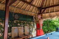 Femme jouant des dards dans le café tropical de Nusa Lembongan, Bali, Indonésie Photos stock