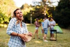 Femme jouant des tambours ayant l'amusement en nature Images stock
