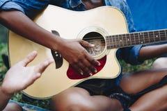 Femme jouant la guitare dans la forêt Photographie stock
