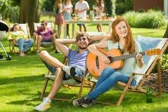 Femme jouant la guitare dans le jardin Image stock