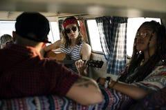 Femme jouant la guitare sur le voyage par la route avec des amis ensemble Photographie stock