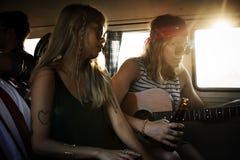 Femme jouant la guitare sur le voyage par la route avec des amis ensemble Images stock