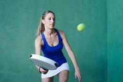 Femme jouant la palette tenant la raquette sportive Photos stock