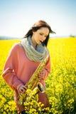 Femme jouant le saxophone dans le domaine de graine de colza Image stock