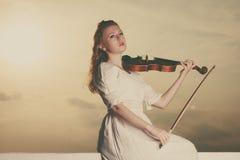 Femme jouant le violon sur le violon près de la plage Image stock