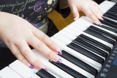 Femme jouant sur un piano Image stock