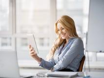 Femme joyeuse à l'aide du dispositif moderne sur le lieu de travail Photos stock